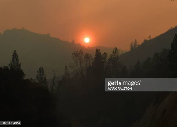 The sun sets over an area partially burnt by the Carr fire as it spreads towards the town of Lewiston near Redding California on Auigust 2 2018...