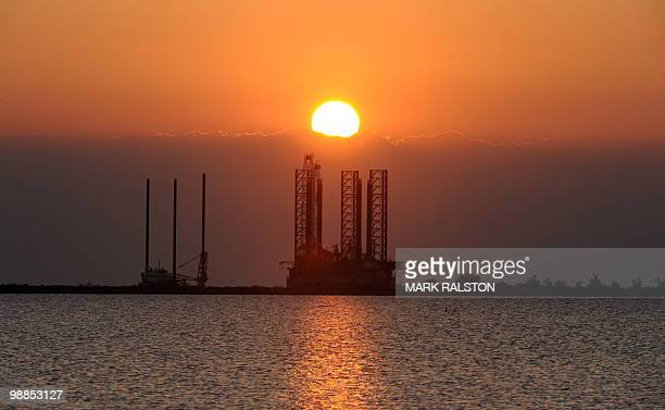 The sun sets over an oil platform waiting to be towed out into the Gulf of Mexico at Port Fourchon in Louisiana on May 4 2010 The world will remain...