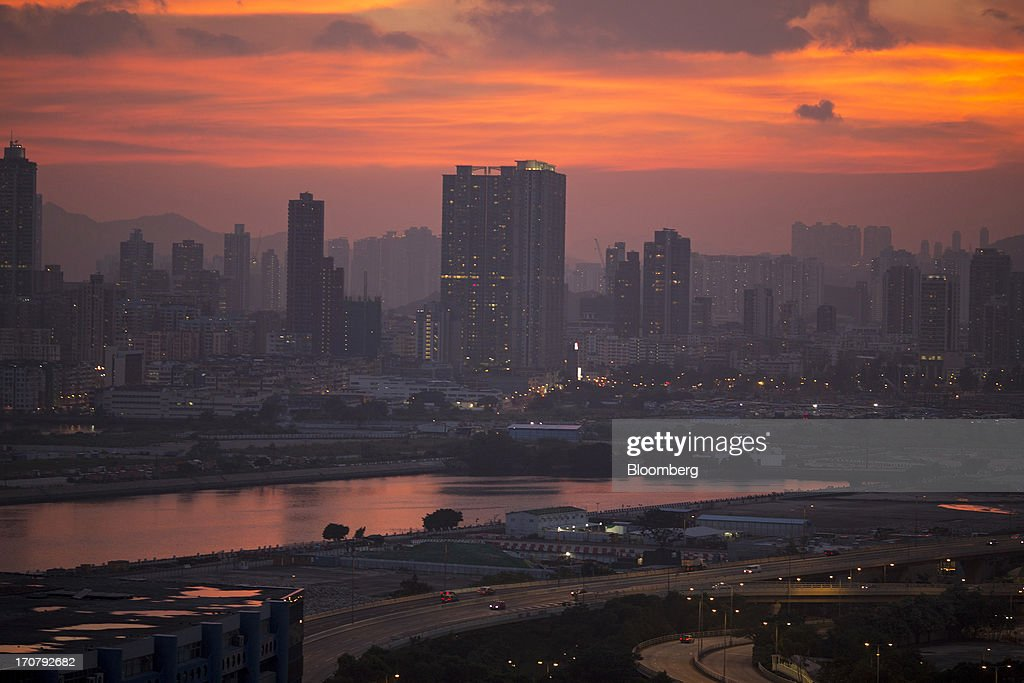 The sun sets over buildings in the Kowloon district of Hong Kong, China, on Wednesday, June 12, 2013. A shortage of housing, low mortgage costs and a buying spree by mainland Chinese have led home prices to more than double since the beginning of 2009, shrugging off repeated attempts by the government to curb gains amid an outcry over affordability. Photographer: Jerome Favre/Bloomberg via Getty Images