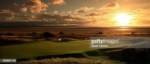 The sun sets over Hilbre Island and the green on the 198 yards par 3 11th hole 'Alps' which will play as the 13th hole in the 2014 Open Championship...