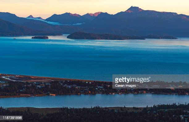 the sun sets over homer alaska with views of islands in kachemack bay - home run ストックフォトと画像