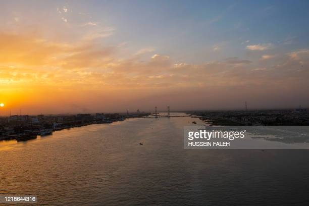 The sun sets over Iraq's southern port city of Basra on June 8, 2020.