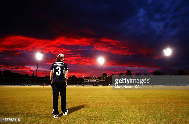 The Sun sets over Manukla Oval as Kelly Applebee fields during the women's T20 match between the ACT and Victoria at Manuka Oval on October 24, 2014...