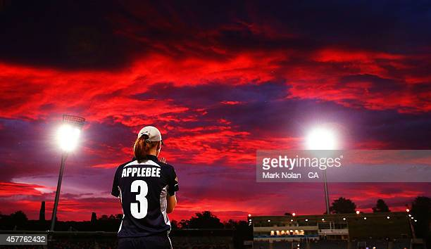The Sun sets over Manukla Oval as Kelly Applebee fields during the women's T20 match between the ACT and Victoria at Manuka Oval on October 24 2014...