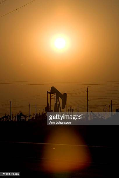 The sun sets over pumpjacks extract oil from an oil field in Lost Hills, California.