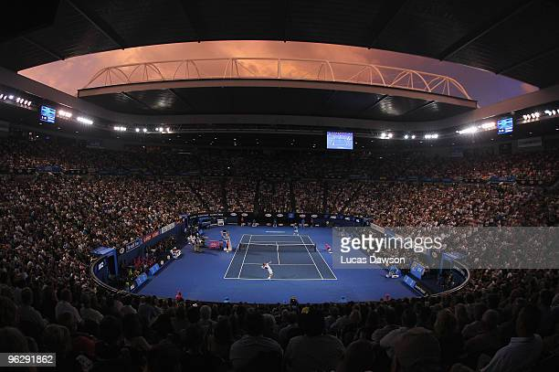 The sun sets over Rod Laver Arena as Andy Murray of Great Britain serves in his men's final match against Roger Federer of Switzerland during day...