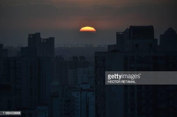 TOPSHOT The sun sets over Shanghai on September 19 2019