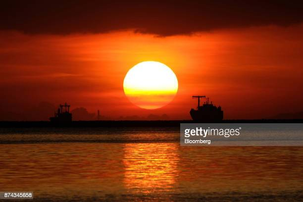 The sun sets over silhouetted boats on the horizon in Manila Bay in Manila Philippines on Sunday Nov 12 2017 Economists are forecasting the...