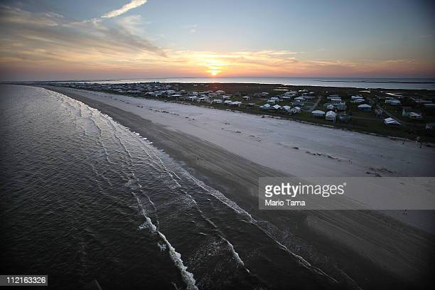 The sun sets over the beach as waves wash up from the Gulf of Mexico April 13 2011 in Grand Isle Louisiana Oil from the BP oil spill washed up onto...