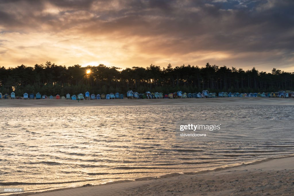 The Sun Sets Over Beach Huts On North Norfolk Coast At Wells Next