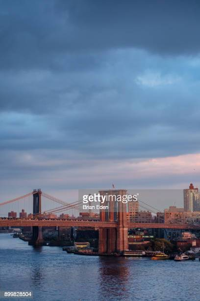 The sun sets over the Brooklyn Bridge in New York City