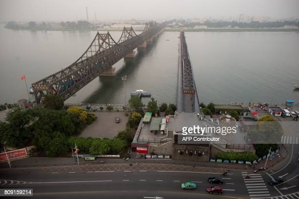 The sun sets over the Friendship bridge on the Yalu River connecting the North Korean town of Sinuiju and Dandong in Chinese border city of Dandong...