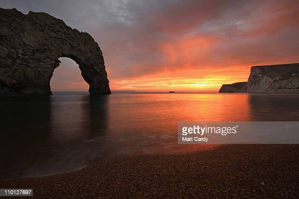 The sun sets over the sea near Durdle Door on March 15 2011 in Dorset England The natural limestone arch near Lulworth in Dorset is one of the...