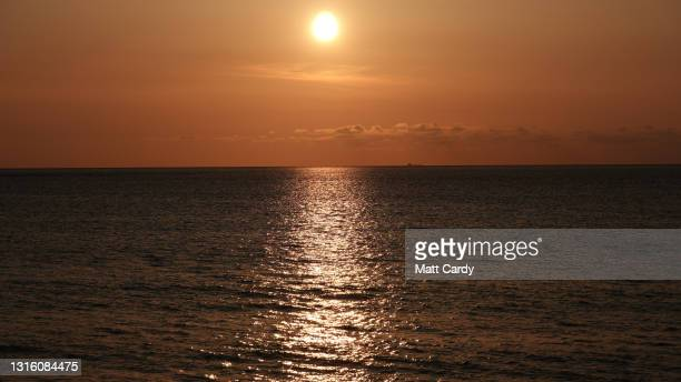 The sun sets over the sea seen from the beach at Sennen Cove on April 17, 2021 in Cornwall, England. With international travel restrictions remaining...