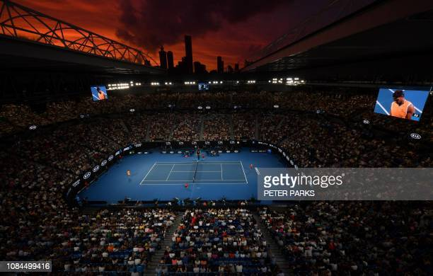 TOPSHOT The sun sets over the skyline as Spain's Rafael Nadal plays Australia's Alex de Minaur during their men's singles match on day five of the...