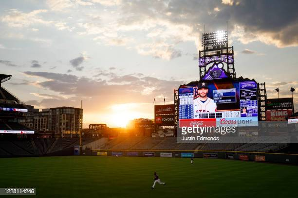 The sun sets over the stadium as Charlie Blackmon of the Colorado Rockies jogs after a foul ball during the third inning against the Houston Astros...
