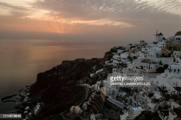The sun sets over the village of Oia on the northwestern tip of the Greek island of Santorini in the Aegean Sea on May 20 2020 The government on May...