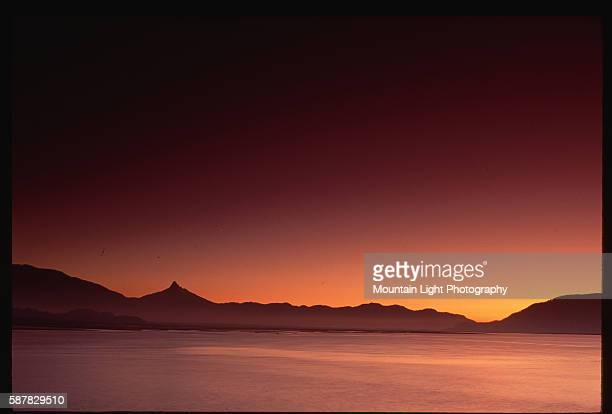 The sun sets over Volcan Corcovado and a lake Chilean Patagonia Chile | Location Los Lagos Region Chile