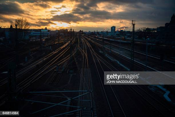 The sun sets railway tracks in Berlin's Westhafen area on March 1 2017 / AFP PHOTO / John MACDOUGALL
