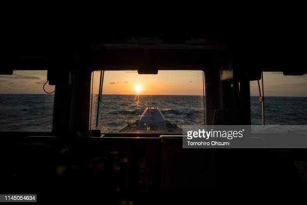 The sun sets seen from the bridge of British Royal Navy's HMS Montrose frigate during a joint exercise with Japanese Maritime Self-Defense Force and...
