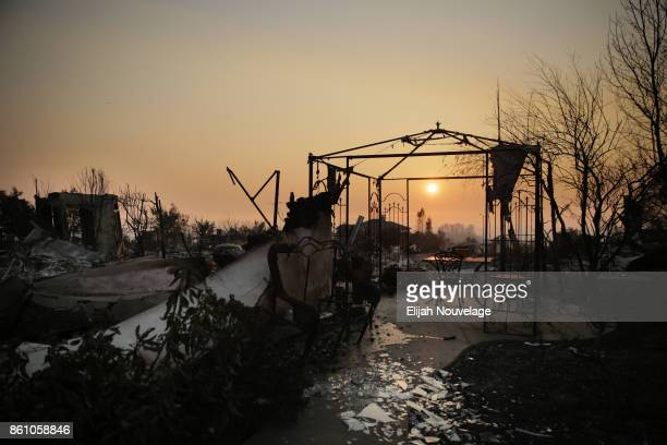 The sun sets through smoke over the remains of homes in the Fountaingrove neighborhood on October 13, 2017 in Santa Rosa, California. Twenty four...