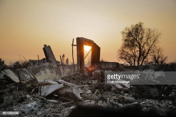 The sun sets through smoke over the remains of homes in the Fountaingrove neighborhood on Oct. 13, 2017 in Santa Rosa, California. Twenty four people...