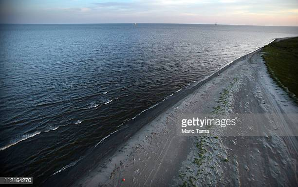 The sun sets waves wash up from the Gulf of Mexico onto the beach April 13 2011 in Isla Grand Terre Louisiana Oil from the BP oil spill washed up...