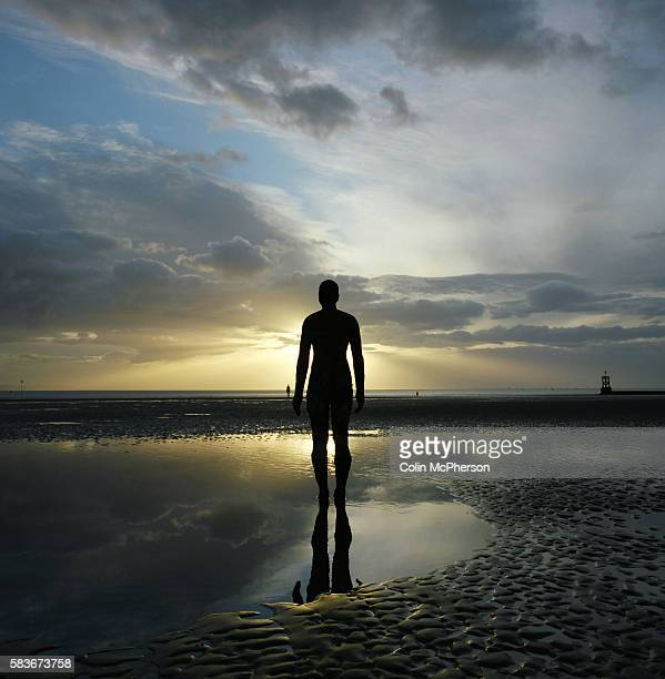 The sun setting behind one of the bronze statues of Antony Gormley's Another Place installation at Crosby Merseyside at the mouth of the river Mersey...