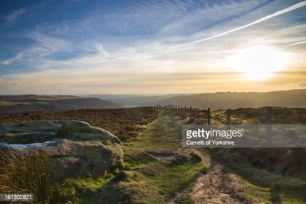The sun setting on Millstone Edge, a gristone edge in the Peak District National Park, Derbyshire, UK. Two walkers can be seen in the distance.