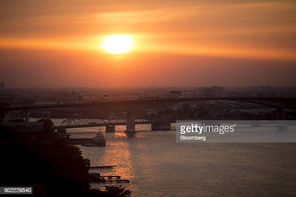 The sun setting over the Rama III bridge front and the Bangkok bridge on the Chao Phraya is seen through the window of a passenger pod on the ferris...