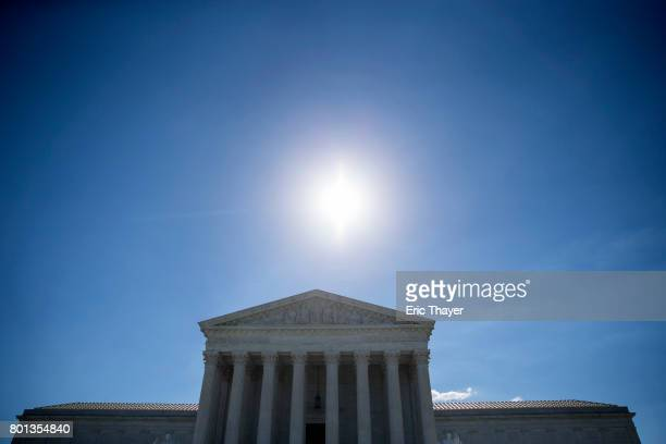 The sun shines above the US Supreme Court after it was announced that the court will allow a limited version of President Donald Trump's travel ban...