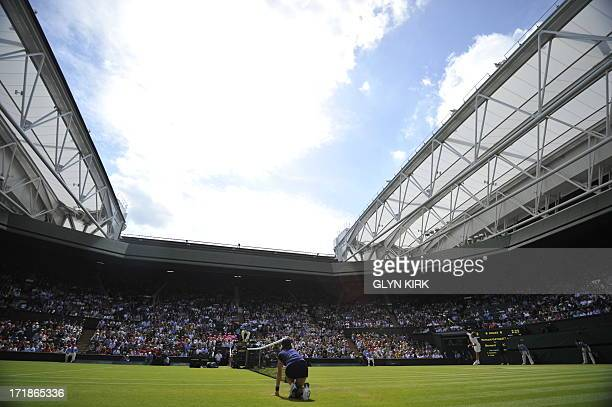 The sun shines down on Centre Court as France's Richard Gasquet serves against Australia's Bernard Tomic in their third round men's singles match on...