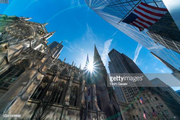 the sun shines from interval of the tips of the st. patrick's cathedral among the midtown manhattan skyscrapers at new york ny usa on apr. 22. - st. patricks cathedral manhattan stock photos and pictures