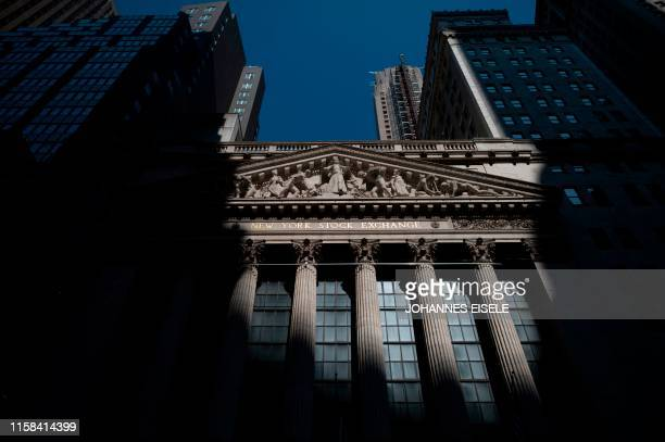 The sun shines on the New York Stock Exchange on July 29, 2019 located at Wall Street in New York City. - Wall Street stocks were mostly lower early...