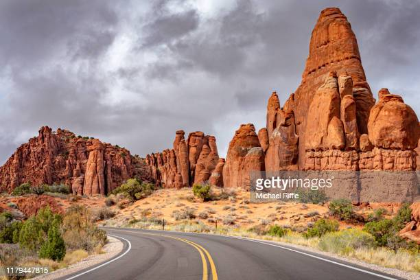 the sun shines on the red rock formations of the fiery furnace area of arches national park with dark storm clouds in the background. - 岩層 ストックフォトと画像