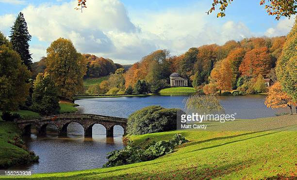 The sun shines on trees that are displaying their autumn colours surrounding Palladian bridge and the lakeside Pantheon at the National Trust's...