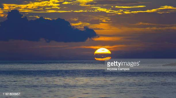 the sun shines over a dramatic sky at sunset on the beach - guanacaste stock pictures, royalty-free photos & images