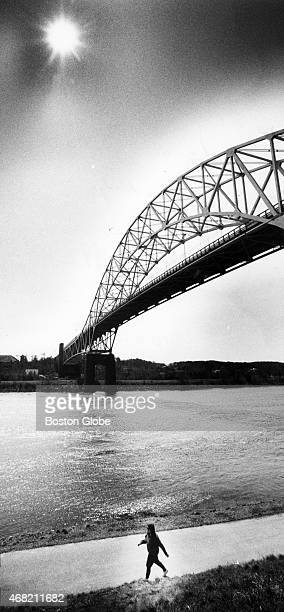 The sun shines over Cape Cod beckoning across the Sagamore Bridge during a woman's walk along the Cape Cod Canal in Borne Mass on April 1 1992
