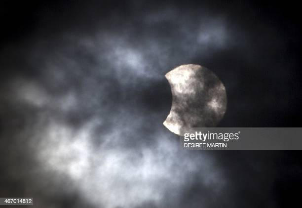 The sun shines through a cloud covered sky as the moon passes infront of the Earth's star marking the begining of a total eclipse the only one this...