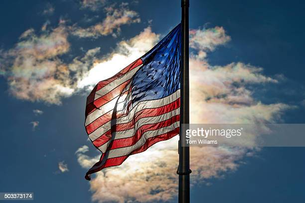 The sun shines through an American flag at the Washington Monument January 4 2016
