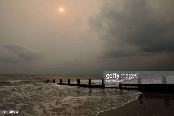 The sun shines through cloud as storm clouds turn the sky black over the sea front on October 16 2017 in Bognor Regis England The West coast of the...