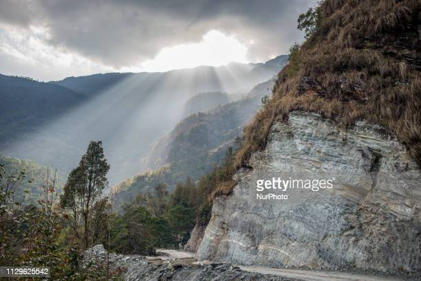 The sun shines through clouds over the mountain road near Pokhara Nepal in March 2019