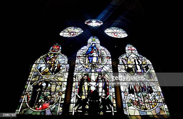 The sun shines through stained glass windows depicting the construction of Southwark Cathedral August 8 2003 in London England The Church of England...
