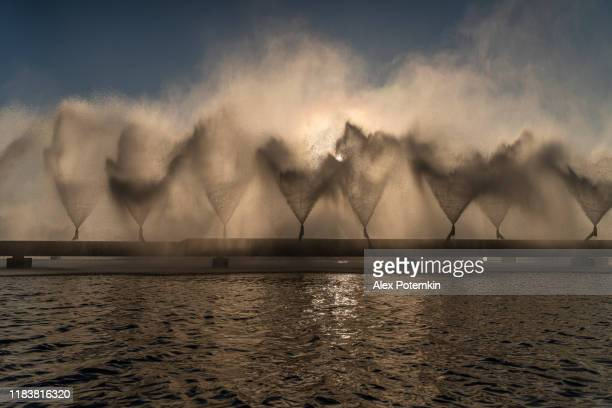 the sun shining through water splashes producing with industrial fountains on cooling basins of the thermal power plant. - fountain stock pictures, royalty-free photos & images