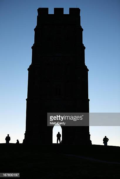 The sun starts to rise as people begin to gather for a Beltane dawn celebration service in front of St Michael's Tower on Glastonbury Tor on May 1...
