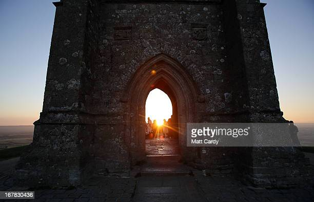 The sun starts to rise as people gather for a Beltane dawn celebration service in front of St Michael's Tower on Glastonbury Tor on May 1 2013 in...