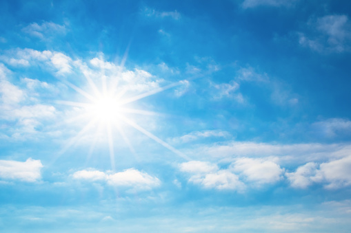 The sun with bright rays in the blue sky with white light clouds. 938231594