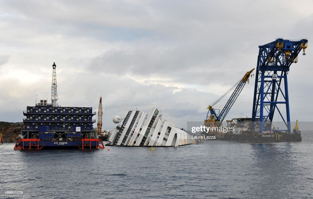 The sunken Costa Concordia remains in the water the day after the commemoration for the victims on January 14, 2013 in Giglio Porto, Italy. It is now a year after the sinking of the ship Costa Concordia. More than four thousand people were on board when the ship hit a rock off the Tuscan coast, killing 32 and leaving two people missing.