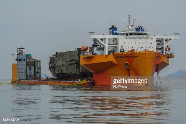 The sunken ferry Sewol is seen on a semisubmersible transport vessel during the salvage operation in waters off Jindo South Korea Salvage crews towed...