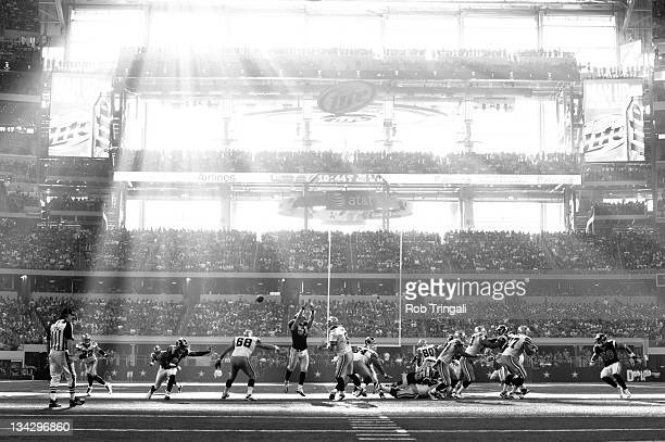 The sunlight beams through the windows down onto the field as Tony Romo of the Dallas Cowboys attempts to complete a pass during the game against the...